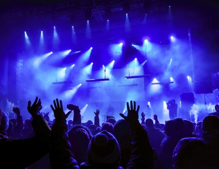 concert audio speaker: Silhouettes of people and musicians in big concert stage. Bright beautiful rays of light