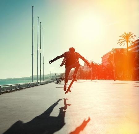 生活方式: 滑板的剪影跳躍在城市的長廊和大海的背景