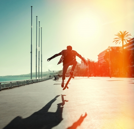 city street: Silhouette of Skateboarder jumping in city on background of promenade and sea Stock Photo