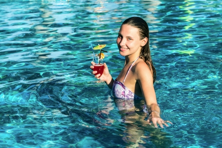Beautiful happy woman with cocktail in pool in hot summer day photo