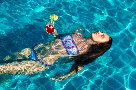 Beautiful woman with cocktail floating in pool on his back, in hot summer day photo
