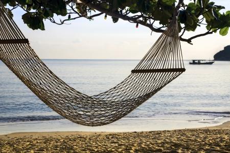 phangan: Hammock hanging on tree on beach ocean. Silhouette of ship on horizon Stock Photo