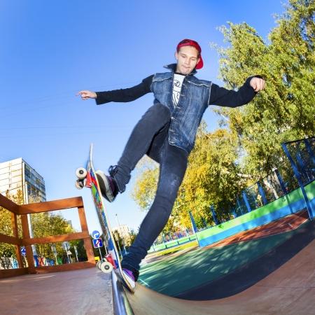 Skateboarder jumping in city skatepark at the halfpipe Stock Photo