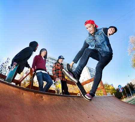 Skateboarder with friends in skatepark jumping in the halfpipe photo