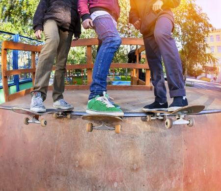 Three friends skateboarders in the halfpipe skatepark