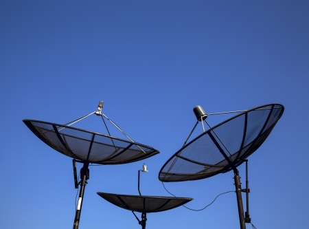 Parabolic satellite antenna on blue sky background photo