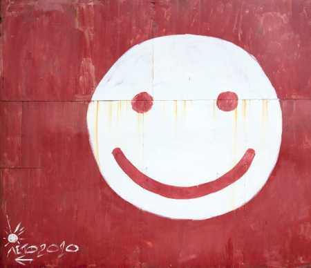 cara sonriente: Símbolo cara sonriente pintada en una cerca