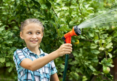 pours: Happy girl pours water from hose, watering  flowers and grass Stock Photo