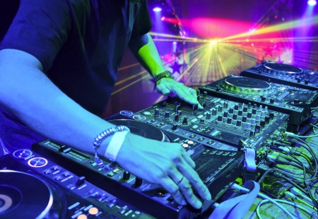 turntables: Dj mixes the track in the nightclub at party. In the background laser light show