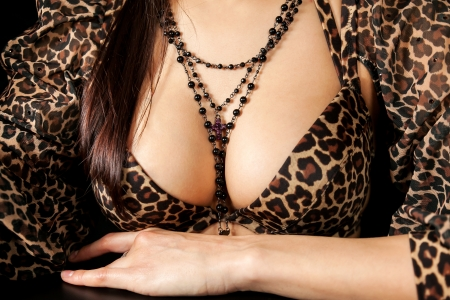 Beautiful attractive young woman with large breasts and necklace on chest
