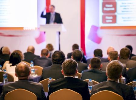 speaker: Altavoz en el podio. La gente en la sala de conferencias. Vista trasera