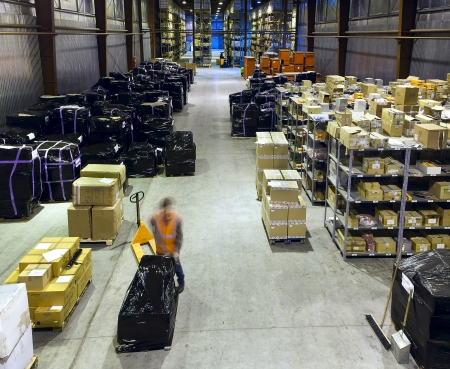 Worker in motion on forklift in large modern warehouse