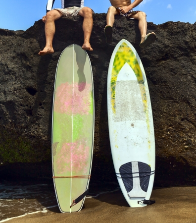 Two friend surfer sitting on rock with his legs dangling photo
