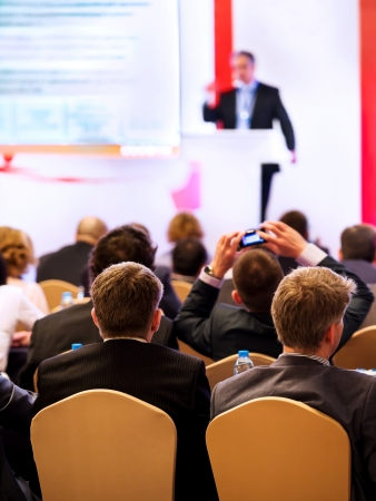 Speaker on the podium. People at the conference hall. Rear view Stock Photo - 24209326
