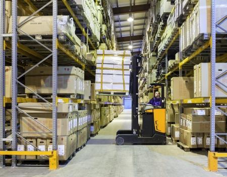 carretillas almacen: Trabajador en la moción sobre la carretilla elevadora en el gran almacén moderno Editorial