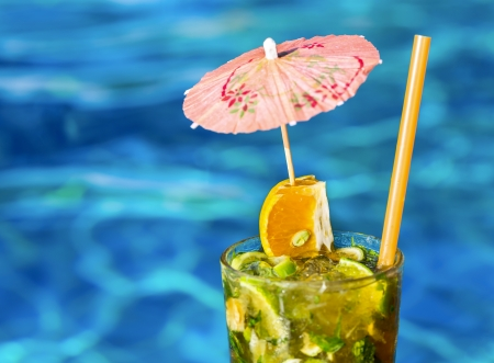 Cocktail Mojito with umbrella near swimming pool photo
