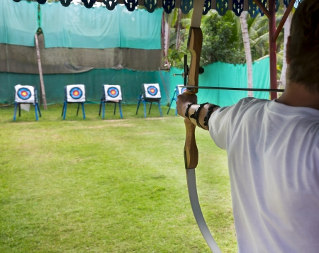 bowstring: Archer man pulls the bowstring and arrow, aiming at a target Stock Photo