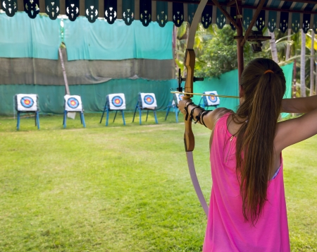 Archer young woman pulls the bowstring and arrow, aiming at a target