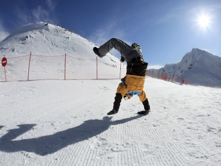 Merry Snowboarder standing on hands in mountains against the blue sky and sun photo