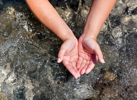 Child scoops up clear water with his hands in river photo