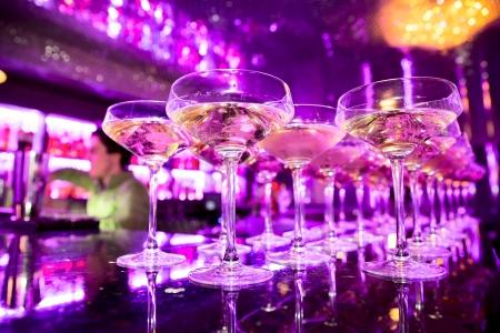 バック グラウンド、ソフト フォーカスで飲み物を作るカクテル バーマン プロ、バーカウンターにシャンパンのグラス 写真素材