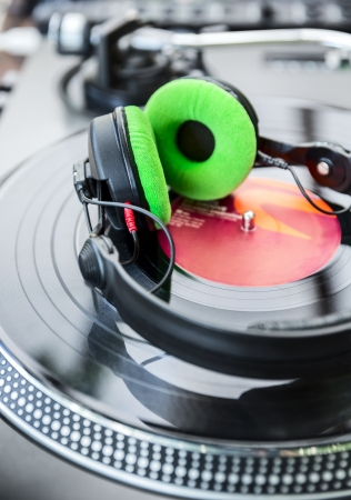 Dj mixer and Vinyl Player with headphones at club. Soft focus photo