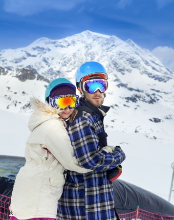 Happy young couple snowboarders in mountains of Alps photo