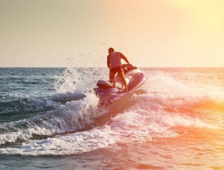 Silhouette of strong man jumps on the jetski above the water at sunset photo