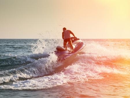 moto acuatica: Silueta del hombre fuerte salta en la jetski por encima del agua al atardecer