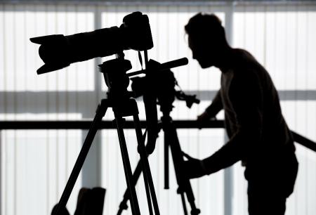 フォトグラファーやカメラマンのシルエットは、屋内の職場で三脚にビデオを撮影
