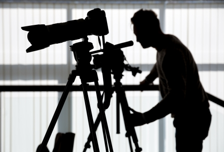 Silhouette of photographer and cameraman shot the video on a tripod at the workplace indoors Archivio Fotografico