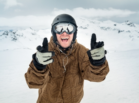 Cheerful snowboarder in protective helmet and mask showing sign happy on the background beautiful mountains photo