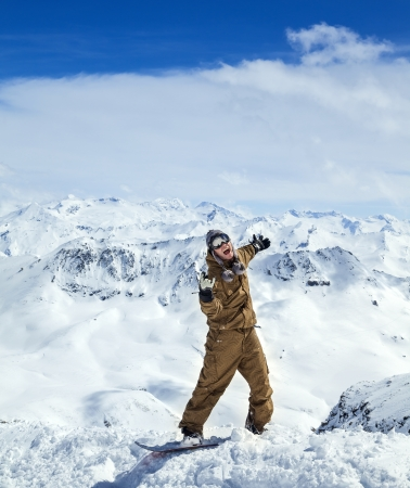 Cheerful snowboarder in protective mask showing sign on the background beautiful mountains and blue sky with clouds photo