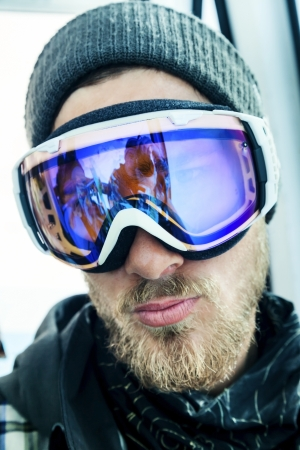 Portrait of a snowboarder with a beard in winter resort in sunglasses mask at ski resort in mountains. Reflection of the photographer photo