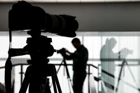 Silhouette der Fotograf und Kameramann erschossen das Video auf einem Stativ am Arbeitsplatz in Innenräumen Standard-Bild - 24354000