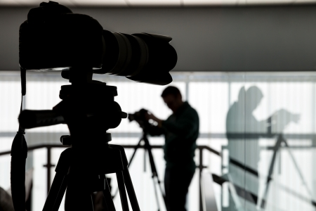 studio photography shot: Silhouette of photographer and cameraman shot the video on a tripod at the workplace indoors Stock Photo