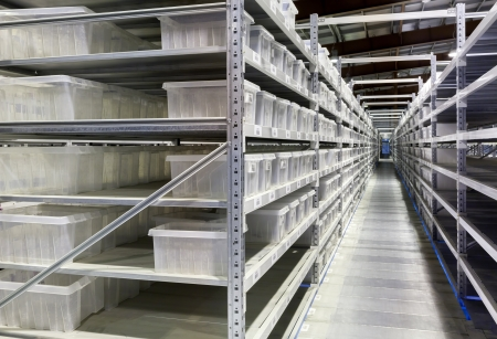 Interior of the new and modern warehouse space in a well lit large room. Rows of shelves with boxes