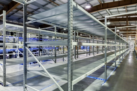 Interior of the new and modern warehouse space in a well lit large room. Rows of empty shelvings