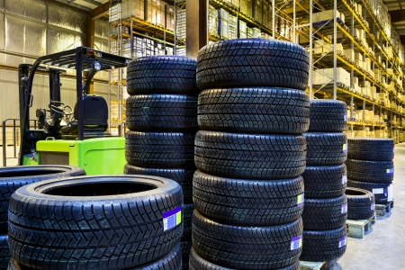 Large modern warehouse with forklifts and stack of car tires Editorial