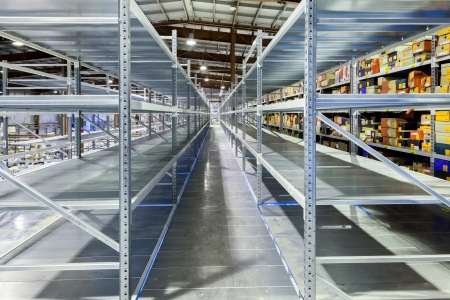 Interior of the new and modern warehouse space in a well lit large room. Rows of empty shelvings and with boxes