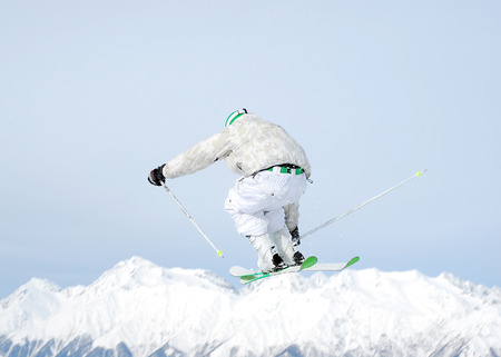 dynamic activity: Jumping skier on the sky. Rear view Stock Photo