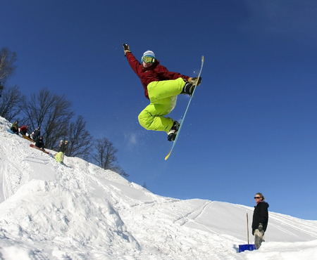 Jumping snowboarder keeps one hand on the snowboard on blue sky