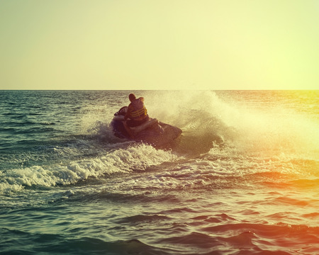jetski: Silhouette of strong man jumps on the jetski above the water at sunset