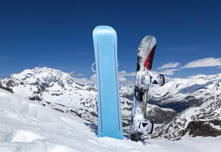 2 つの山の雪の中で直立スノーボードし、青空と雲。ティニュのアルペン スキー リゾート