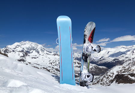 Two snowboard standing upright in the snow on a mountains and blue sky with clouds. The Alpine skiing resort in Tignes Archivio Fotografico