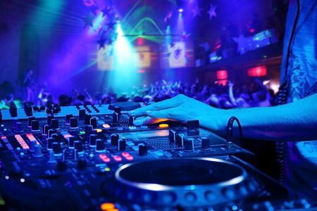 laser show: Dj mixes the track in the nightclub at party On background of people dancing and a laser show Stock Photo