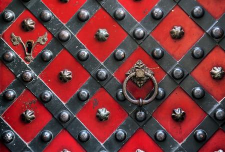 door leaf: Riveted Old red door with handle and lock with metal strips