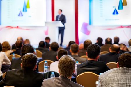 conferentie: Spreker op het podium. Mensen bij conferentiezaal, achteraanzicht