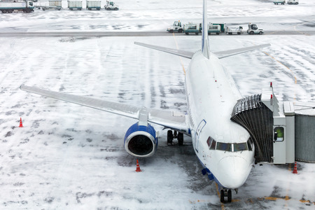 airfield: Passenger Airplane on the airfield winter before takeoff. Sleeve for boarding passengers in the aircraft