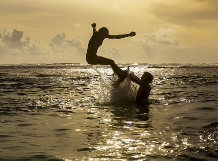 expiring: Silhouette of young girl jumping out of the ocean, which throws strong two man on the background of the expiring sunset